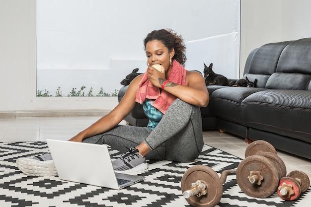 Afroamerykanka lekkoatletka z ręcznikiem na szyi jedząca jabłko po treningu w domu, siedząc na podłodze i oglądając wideo na laptopie