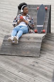 Afroamerykanka łyżwiarka siedzi na drewnianej ławce w przestrzeni miejskiej ze smartfonem czat online na zewnątrz