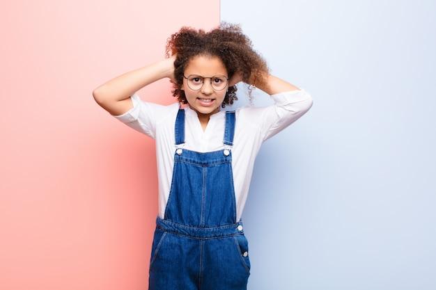 Afroamerykanka mała dziewczynka czuje się zestresowana, zmartwiona, niespokojna lub przestraszona, z rękami na głowie, panikuje podczas pomyłki na płaskiej ścianie