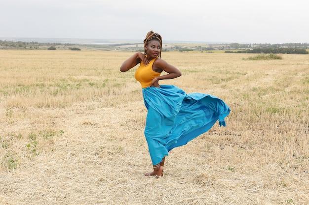 Afroamerykanka młoda kobieta bawi się na świeżym powietrzu o zachodzie słońca