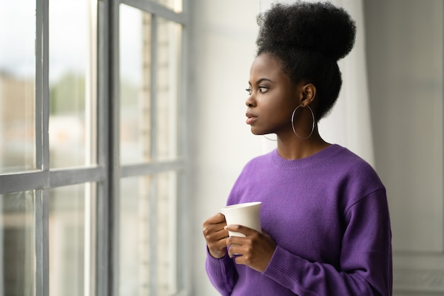 Afroamerykanka myśli, patrząc przez okno, trzymając kubek, pijąc kawę