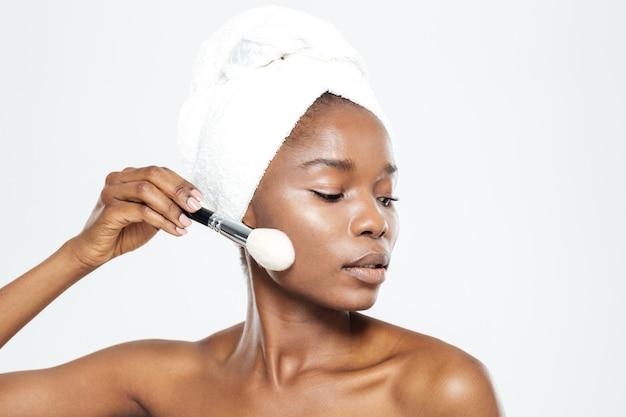 Afroamerykanka nakładająca makijaż pędzlem na białym tle na białym tle