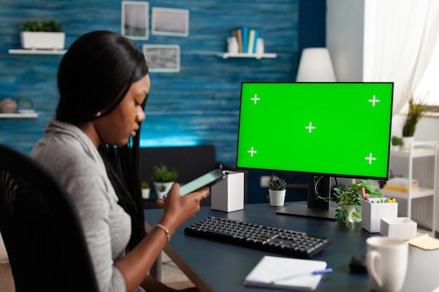 Afroamerykanka przeglądająca informacje o szkole na telefonie pracującym zdalnie z domu
