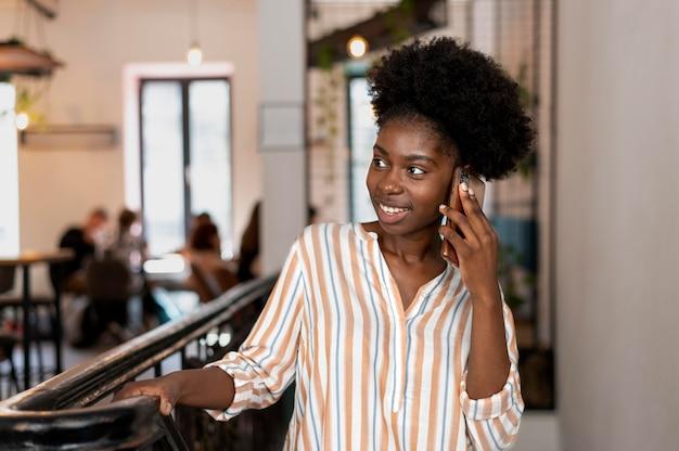 Afroamerykanka rozmawia z kimś na swoim smartfonie
