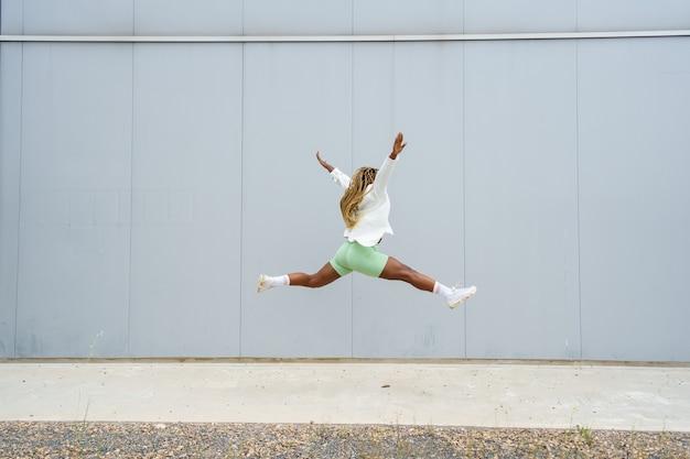 Afroamerykanka skacząca swobodnie obok muru miejskiego w bluzce i szortach