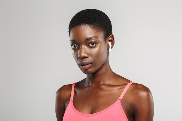 Afroamerykanka sportsmenka używająca bezprzewodowych słuchawek i patrząca na kamerę odizolowaną nad białą ścianą
