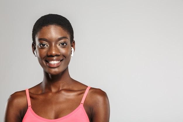 Afroamerykanka sportsmenka używająca bezprzewodowych wkładek dousznych i uśmiechająca się na białym tle nad białą ścianą