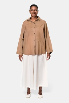 Afroamerykanka ubrana w brązową koszulę z długim rękawem i białymi spodniami typu culotte