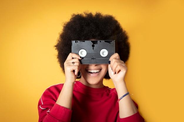 Afroamerykanka, uśmiechnięta, ubrana w zwykłe ubranie, trzymająca retro taśmę wideo, przykłada ją do twarzy
