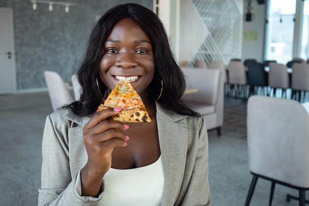 Afroamerykanka w garniturze jedząca pizzę