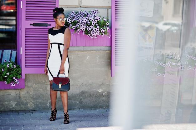 Afroamerykanka w okularach, czarno-białej sukni i torebce postawionej na fioletowe okna.