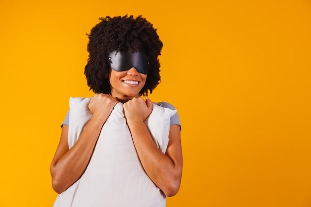 Afroamerykanka w piżamie i masce do spania przytula poduszkę i uśmiecha się na żółtym tle