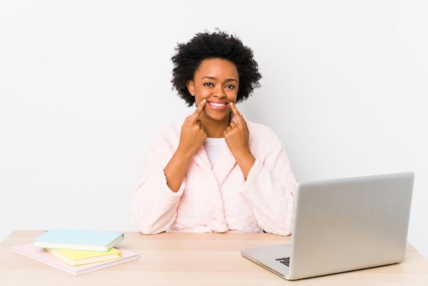 Afroamerykanka w średnim wieku pracująca w domu na białym tle wątpiąca między dwiema opcjami.