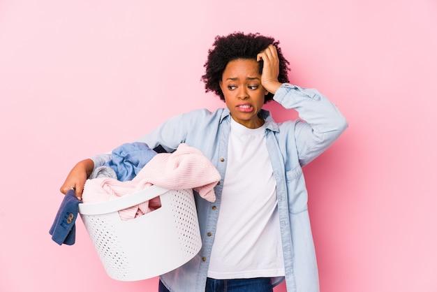 Afroamerykanka w średnim wieku robi pranie będąc zszokowana, pamiętała ważne spotkanie.