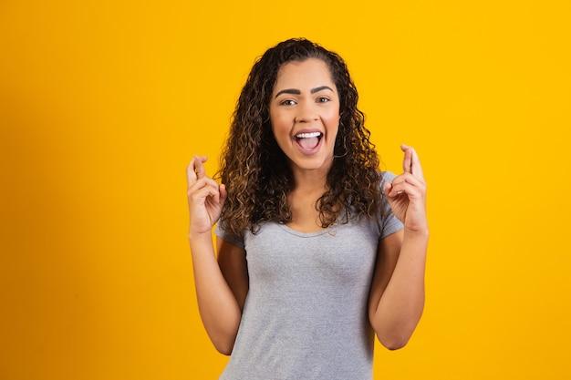 Afroamerykanka z afro włosami gestykuluje ze skrzyżowanymi palcami, uśmiechając się z nadzieją. koncepcja szczęścia i przesądów.