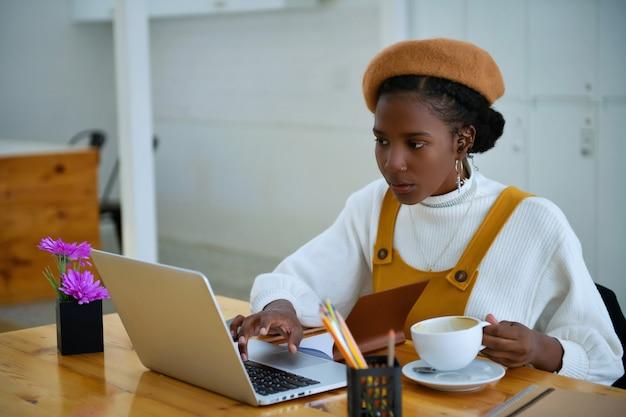 Afroamerykanki biznesu używają laptopów do pracy w biurze - czarnoskórzy
