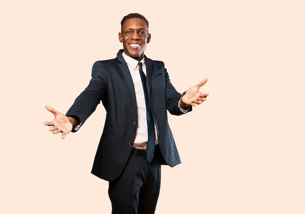 Afroamerykanów biznesmen uśmiecha się wesoło, dając ciepły, przyjazny, kochający uścisk powitalny, czując się szczęśliwy i uroczy na beżowej ścianie