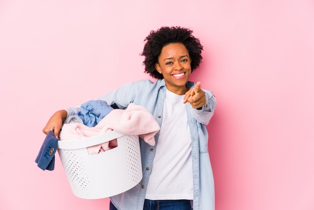 Afroamerykanów wieku średniego kobieta robi pranie na białym tle wesoły uśmiechy wskazujące na przód.
