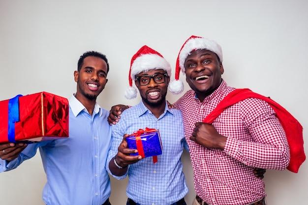 Afroamerykańscy mężczyźni w santa hat z pudełkiem na białym tle studio.ciemnoskóry święty mikołaj wesołych świąt z workiem pełnym świątecznych gadżetów. trzej przyjaciele świętują nowy rok