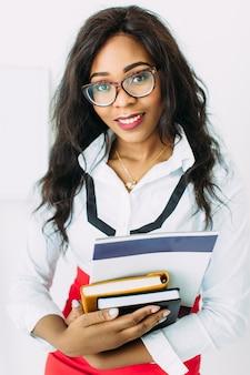 Afroamerykańska biznesowa kobieta trzyma książki i dokumenty w szkłach