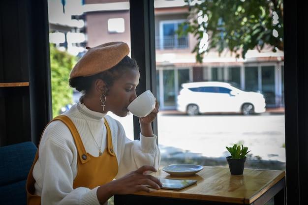 Afroamerykańska bizneswoman używa tabletu do rozmowy z klientami w kawiarni i trzyma w ręku filiżankę kawy.
