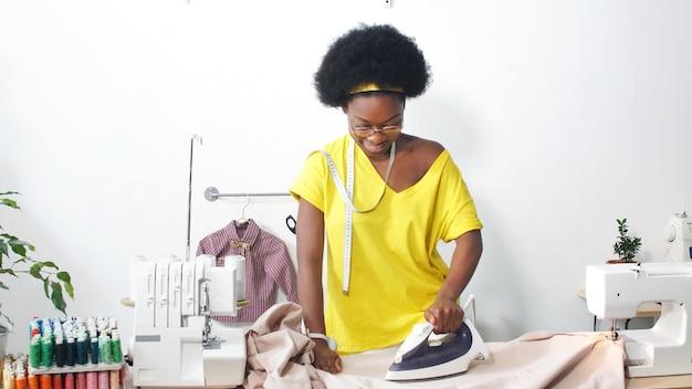 Afroamerykańska krawcowa wygładza materiał żelazkiem w swoim miejscu pracy, miejscu pracy krawcowej w warsztacie