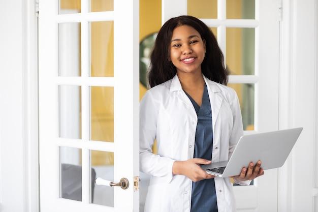 Afroamerykańska lekarka udziela konsultacji telemedycznych poprzez transmisję informacji medycznych kanałami telekomunikacyjnymi wysokiej jakości materiału filmowego