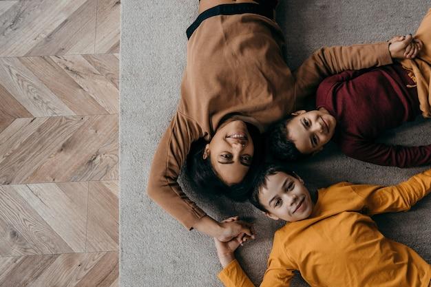 Afroamerykańska mama i dwaj synowie leżą na podłodze i patrzą w kamerę. wysokiej jakości zdjęcie