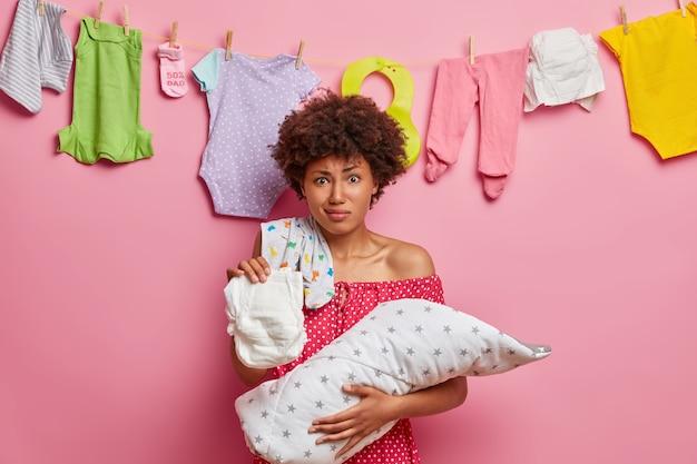 Afroamerykańska mama trzyma brudną pieluchę i czuje niechęć, bierze akr niemowlęcia, które śpi w ciągu dnia, zajęty karmieniem noworodka, stoi pod różową ścianą, wiesza wyprane ubrania dla niemowląt za