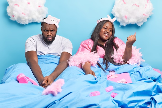 Afroamerykańska para pozuje na wygodnym łóżku pod kocem, przygotowując się do snu na niebieskim tle