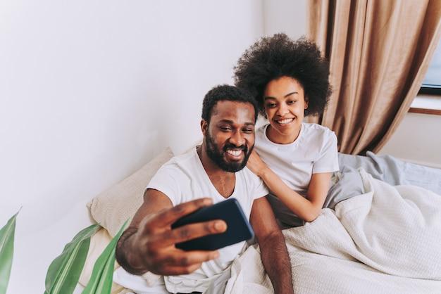 Afroamerykańska para w łóżku prawdziwa piękna i wesoła para kochanków w domu