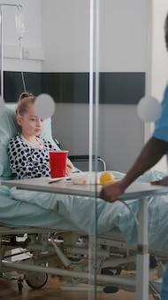 Afroamerykańska pielęgniarka przynosząca zdrowy posiłek dla chorego pacjenta