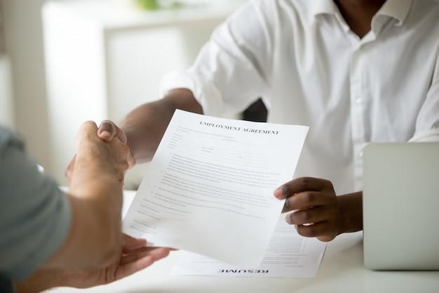 Afroamerykańska pracodawca trzyma zatrudnienie zgody handshaking kandydata, zamyka w górę widoku