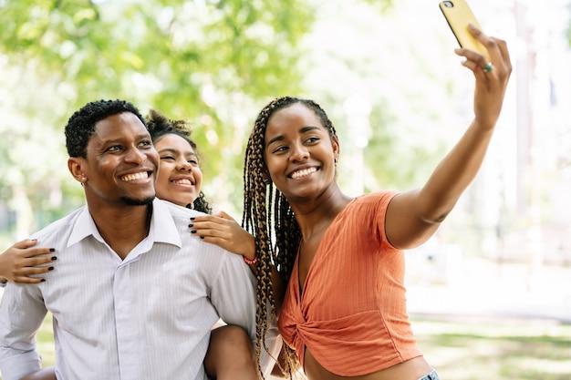 Afroamerykańska rodzina bawi się i cieszy dzień w parku, robiąc selfie razem z telefonem komórkowym.