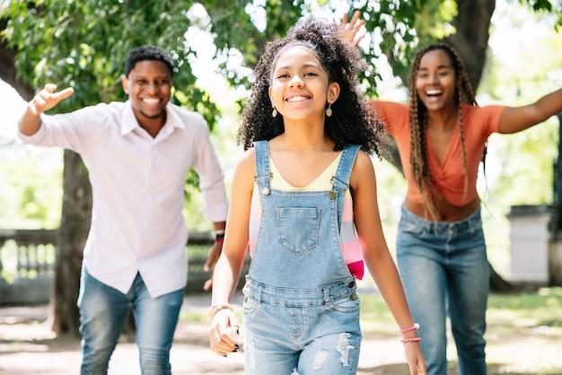 Afroamerykańska rodzina bawi się i spędza razem dzień na świeżym powietrzu w parku.