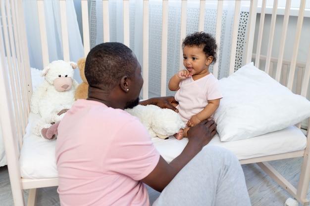 Afroamerykańska rodzina, tata i synek rozmawiają lub bawią się w sypialni w domu, szczęśliwy ojciec
