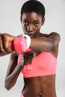 Afroamerykańska sportsmenka ćwicząca z hantlami na białym tle nad białą ścianą