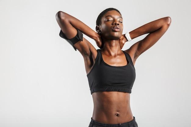 Afroamerykańska sportsmenka robi ćwiczenia podczas ćwiczeń na białym tle nad białą ścianą