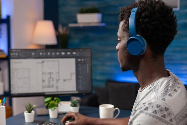 Afroamerykański architekt pracownik z zestawem słuchawkowym siedzący przy biurku w salonie