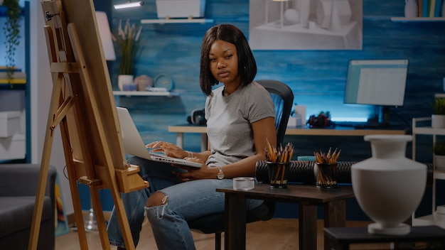 Afroamerykański artysta piszący na komputerze przenośnym w studio