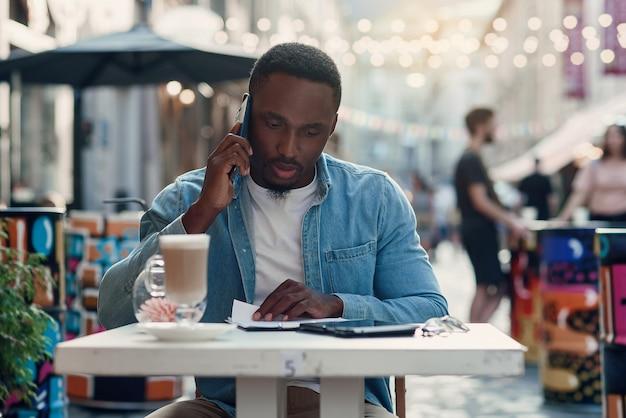Afroamerykański biznesmen czyta papierowe dokumenty i pracuje na laptopie siedząc w kawiarni na świeżym powietrzu z