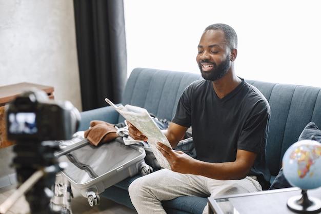Afroamerykański bloger siedzący przed kamerą i nagrywający film o swoim bagażu