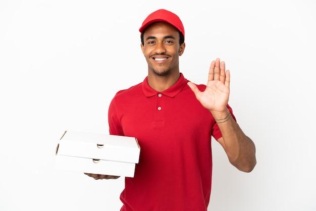 Afroamerykański dostawca pizzy, który podnosi pudełka po pizzy nad odosobnioną białą ścianą pozdrawiając ręką z radosnym wyrazem twarzy
