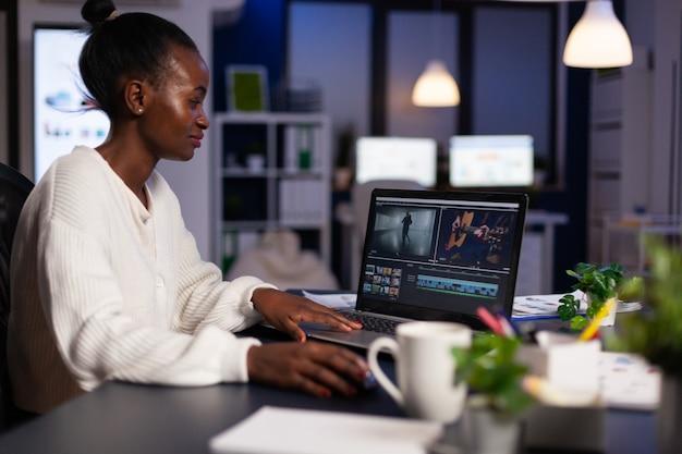 Afroamerykański edytor wideo pracujący późno w nocy przy cyfrowym projekcie filmowym