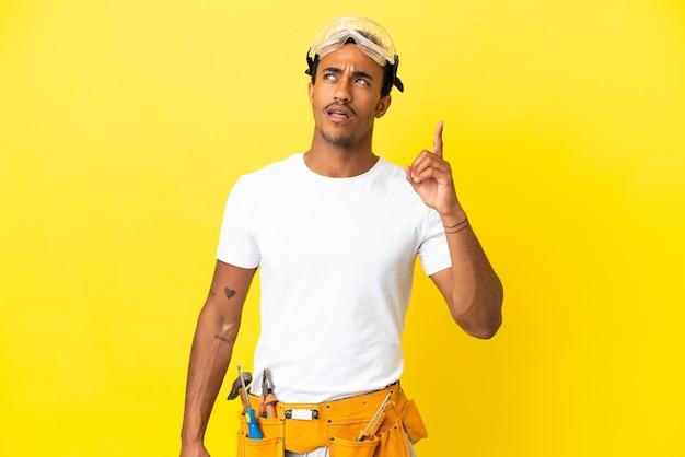 Afroamerykański elektryk mężczyzna nad odosobnioną żółtą ścianą, myślący o pomyśle wskazującym palec w górę