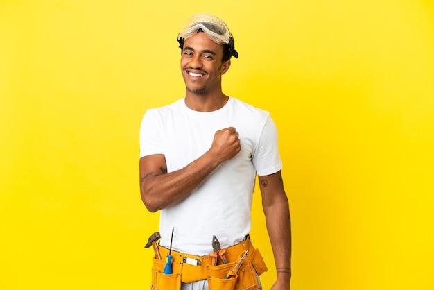 Afroamerykański elektryk mężczyzna nad odosobnioną żółtą ścianą świętuje zwycięstwo