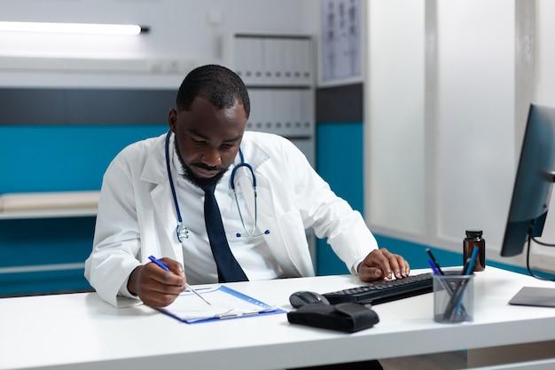 Afroamerykański lekarz lekarz wpisując leczenie opieki zdrowotnej na komputerze