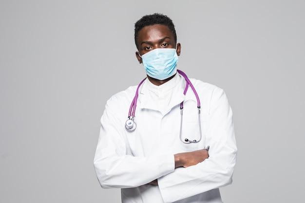 Afroamerykański lekarz medycyny mężczyzna z maską odizolowywającą na szarym tle