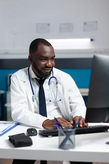 Afroamerykański lekarz specjalista analizujący ekspertyzę dotyczącą choroby na komputerze