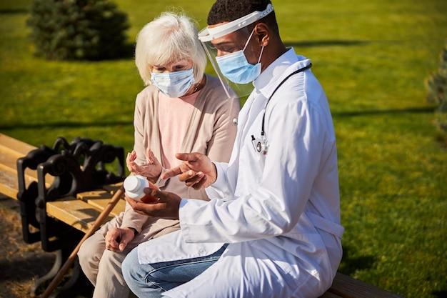 Afroamerykański lekarz wskazujący palcem na lek w dłoni i wskazujący właściwy sposób jego przyjmowania